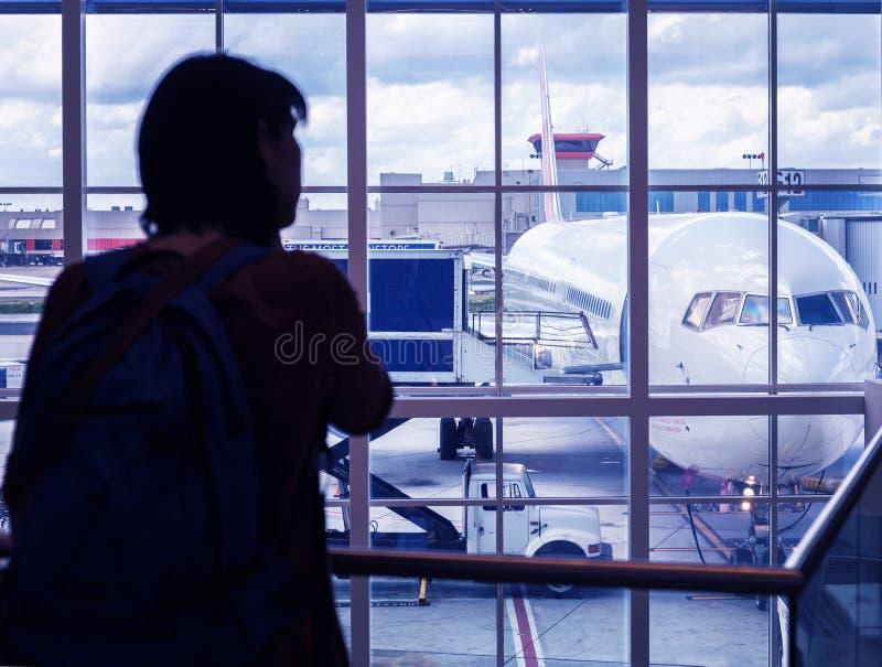 Siluetee a una mujer joven está defendiendo en el aeropuerto la ventana que mira la preparación prevuela de los aviones imágenes de archivo libres de regalías