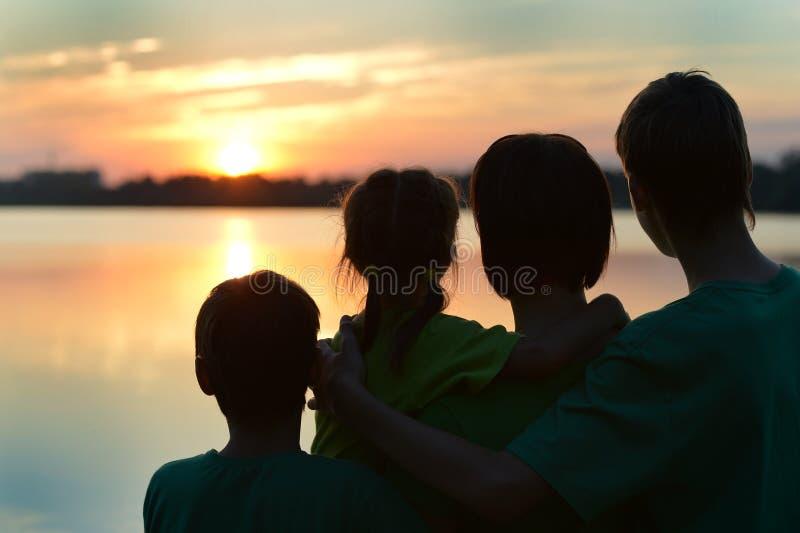 Siluetta, bambini felici con la madre e padre fotografie stock