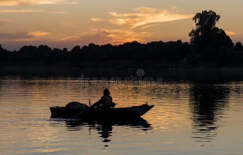 Siluetta beduina egiziana tradizionale del pescatore al tramonto immagini stock