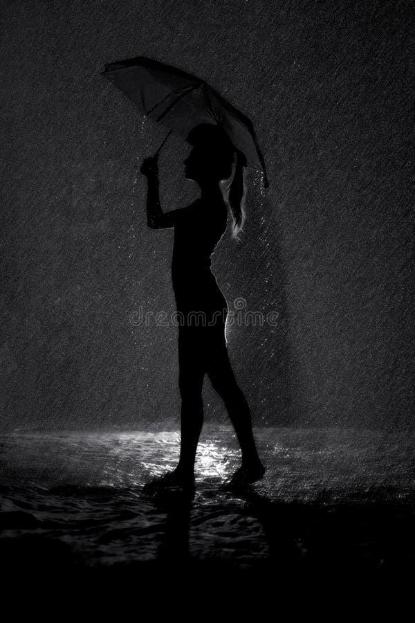 Siluetta in bianco e nero della figura di una ragazza con un ombrello nella pioggia, nel tempo di concetto e nell'umore fotografie stock libere da diritti