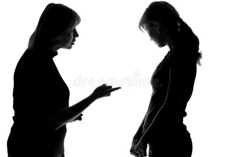 Siluetta in bianco e nero di una madre che rimprovera e fa la figlia inesperta fotografia stock libera da diritti