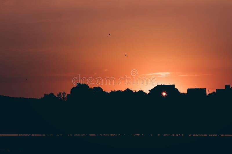 Siluetta, casa rurale al tramonto immagine stock