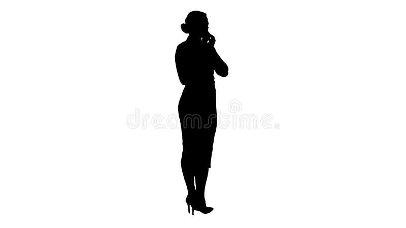 Siluetta che sta giovane bella donna che per mezzo di un telefono cellulare che fa una chiamata fotografia stock libera da diritti