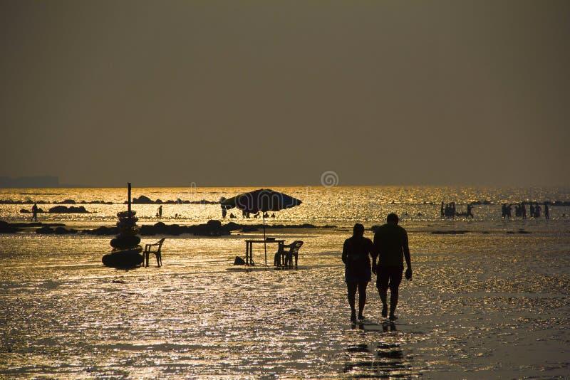 Siluetta con le coppie che camminano sulla spiaggia, sull'acqua di mare brillante e sull'altra gente, spiaggia di Kihim, Alibag immagine stock