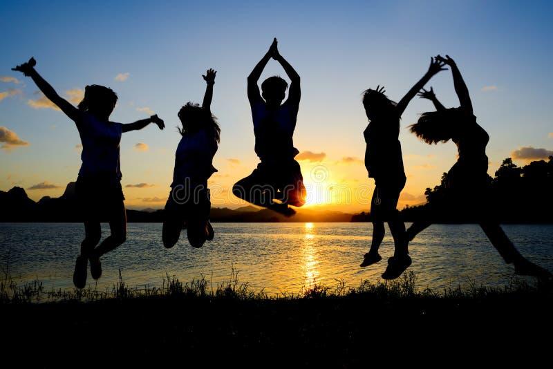 Siluetta degli amici che saltano nel tramonto immagine stock