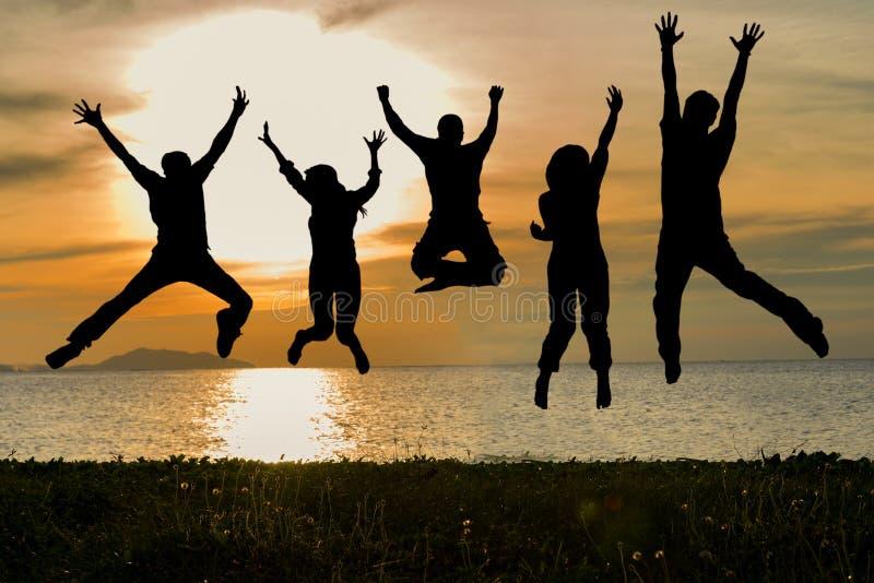 Siluetta degli amici e del lavoro di squadra che saltano sulla spiaggia durante il tempo di tramonto per l'affare di successo fotografia stock libera da diritti