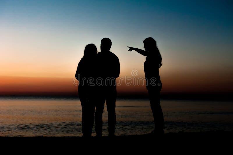 Siluetta degli amici sulla spiaggia immagini stock libere da diritti