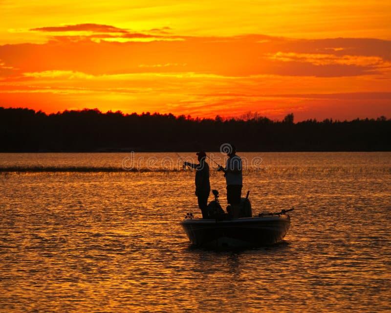 Siluetta degli uomini che pescano in una barca sul lago dopo il tramonto immagini stock