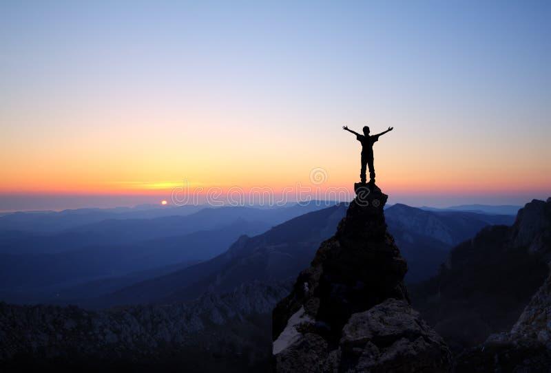 Siluetta degli uomini in cima alla montagna immagini stock