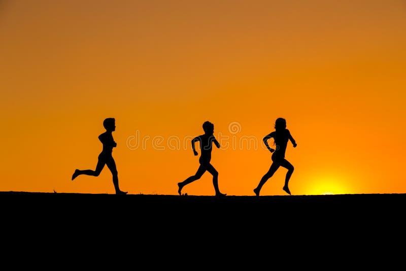 Siluetta dei bambini che corrono contro il tramonto immagini stock