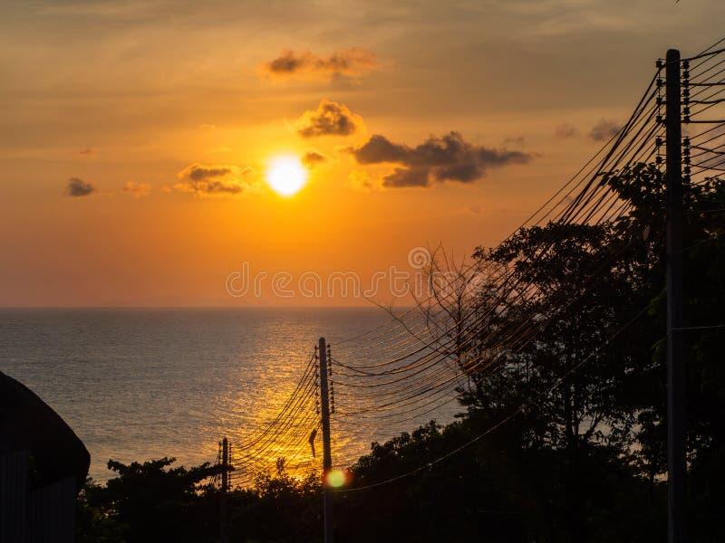 Siluetta dei cavi elettrici contro la regolazione del sole nel mare immagine stock