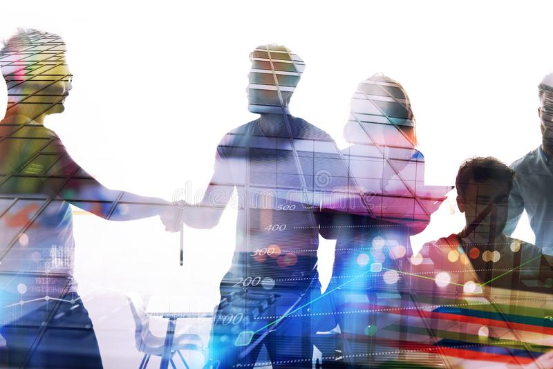 Siluetta dei giovani operai che stringono le mani nell'ufficio Concetto di lavoro di squadra e dell'associazione Doppia esposizio fotografia stock