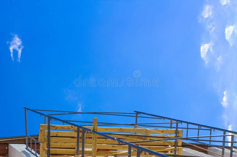 Siluetta dei muratori su funzionamento dell'impalcatura sotto un cielo blu fotografia stock