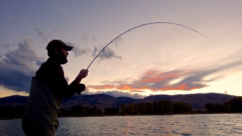Siluetta dei pescatori di una mosca fotografia stock