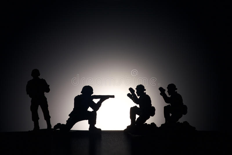 Siluetta dei soldati su un fondo scuro immagine stock