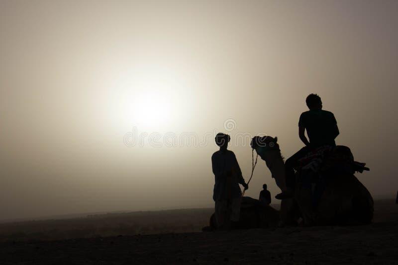 Siluetta dei turisti e del cammello fotografie stock libere da diritti