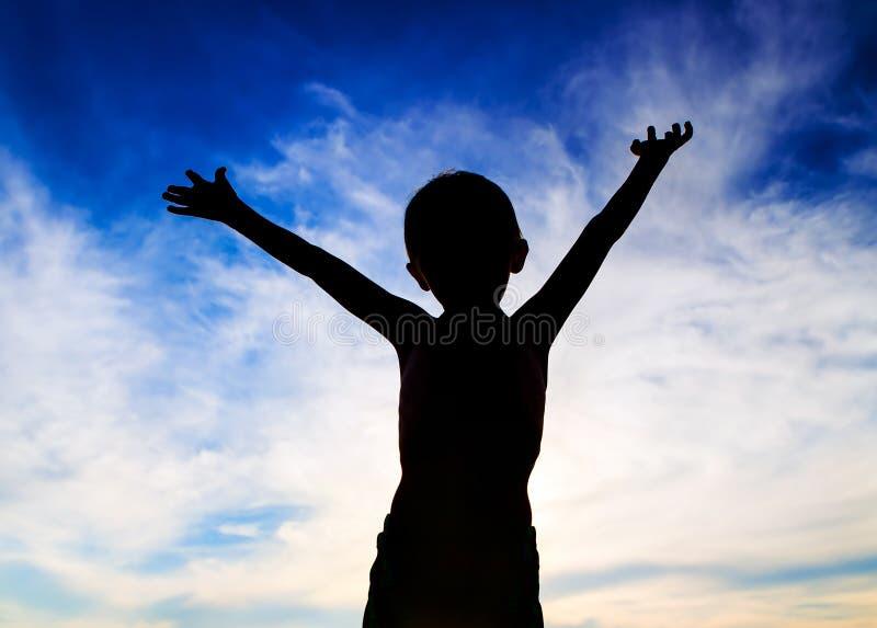 Siluetta del bambino con le mani su fotografie stock