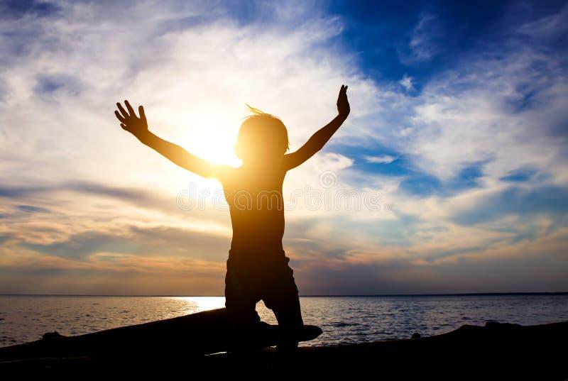 Siluetta del bambino con le mani su fotografie stock libere da diritti