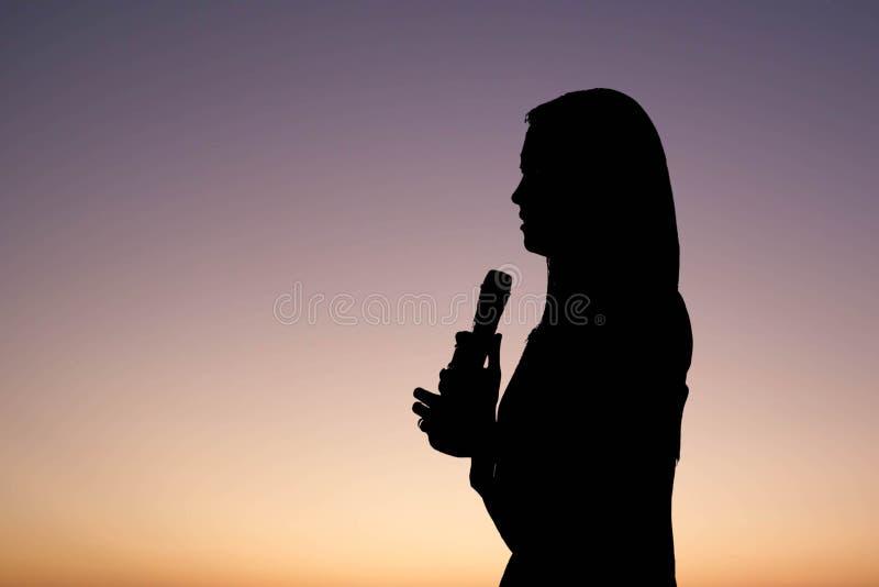Siluetta del cantante o dell'altoparlante della donna illustrazione di stock