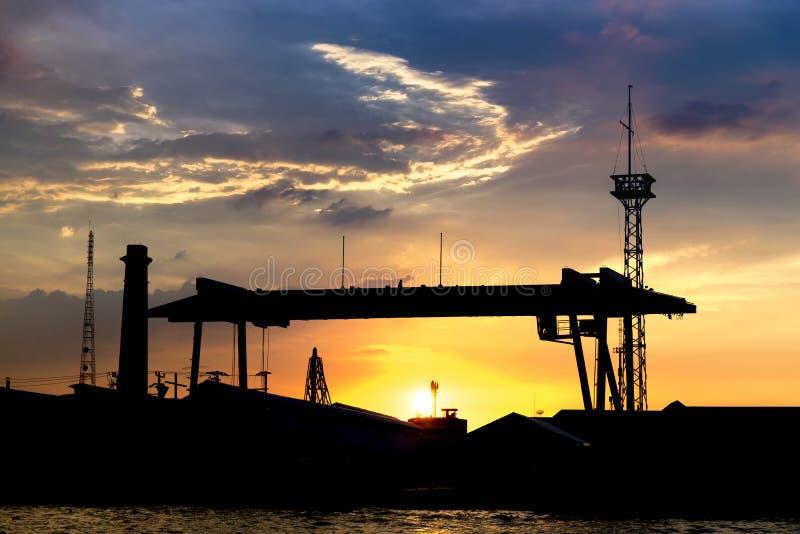 siluetta del cantiere navale con il fondo di schermo di aumento sole/di tramonto fotografia stock libera da diritti
