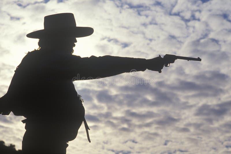 Siluetta del cowboy che tende pistola fotografie stock libere da diritti