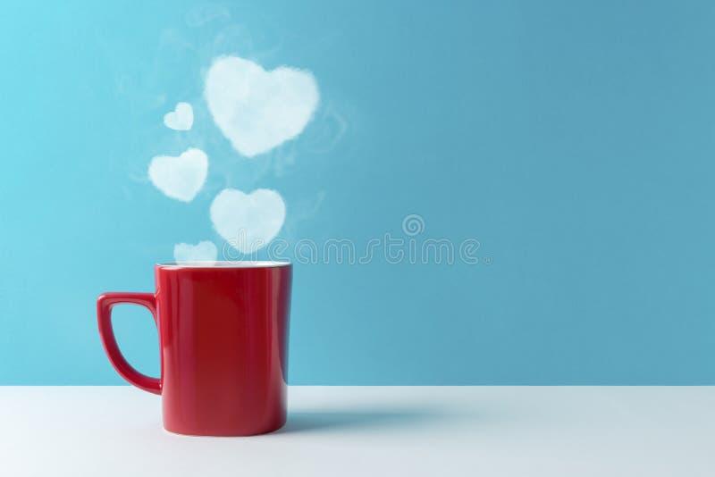 Siluetta del cuore fatta di cottura a vapore caffè o della bevanda calda su fondo blu immagini stock