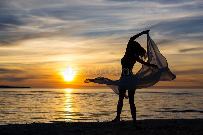 Siluetta del dancing esile della donna con la sciarpa sulla spiaggia fotografie stock