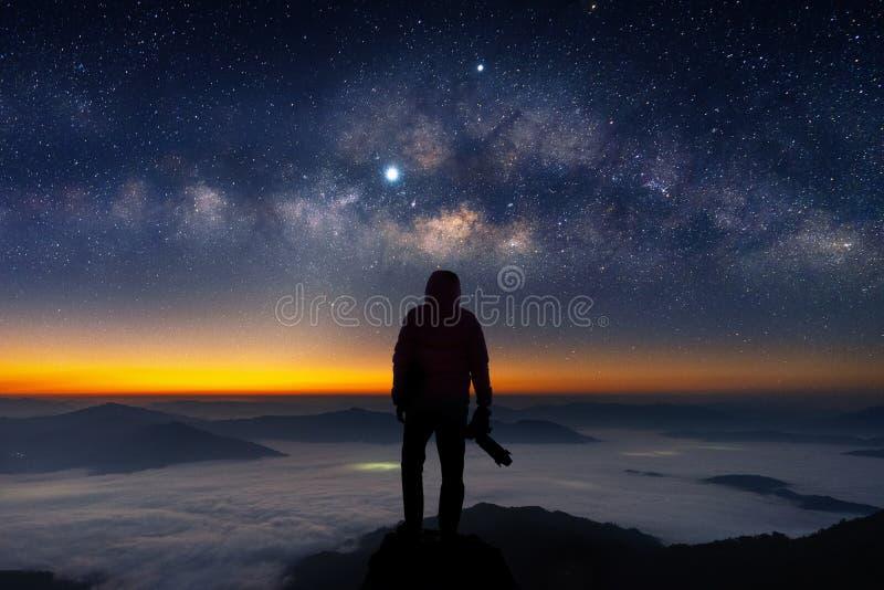 Siluetta del fotografo con il blackground della Via Lattea e della macchina fotografica fotografia stock libera da diritti