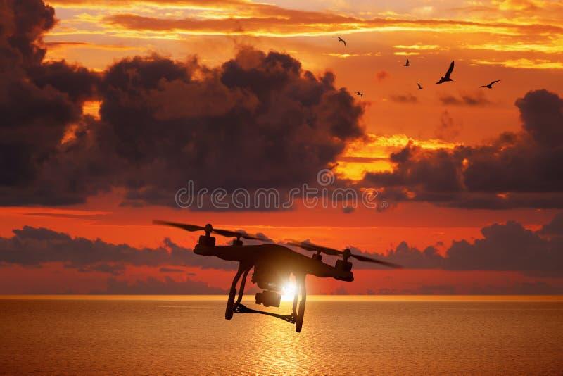 Siluetta del fuco di volo in cielo rosso d'ardore di tramonto sopra il mare fotografie stock