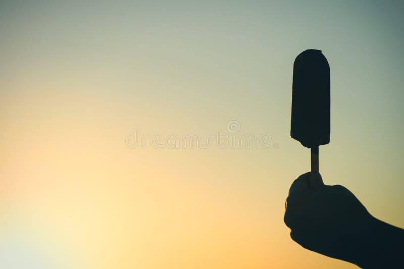 Siluetta del gelato sul bastone a disposizione sul fondo di tramonto immagini stock libere da diritti