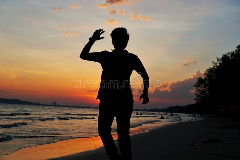 Siluetta del giovane che salta alla spiaggia che ha tramonto nelle vacanze estive fotografie stock