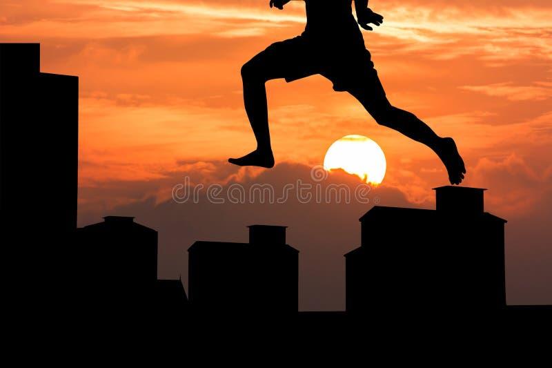 Siluetta del giovane che salta sul backgro di tramonto del buildingat fotografie stock libere da diritti