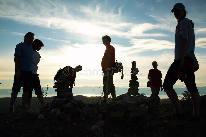 Siluetta del gruppo di persone in cima alla montagna fotografia stock libera da diritti