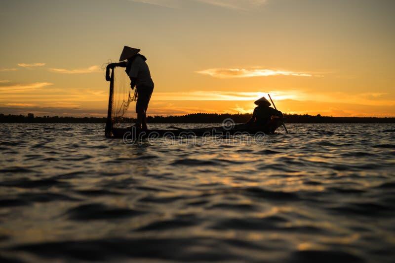 Siluetta del lago netto di lancio di pesca del pescatore tradizionale a immagini stock