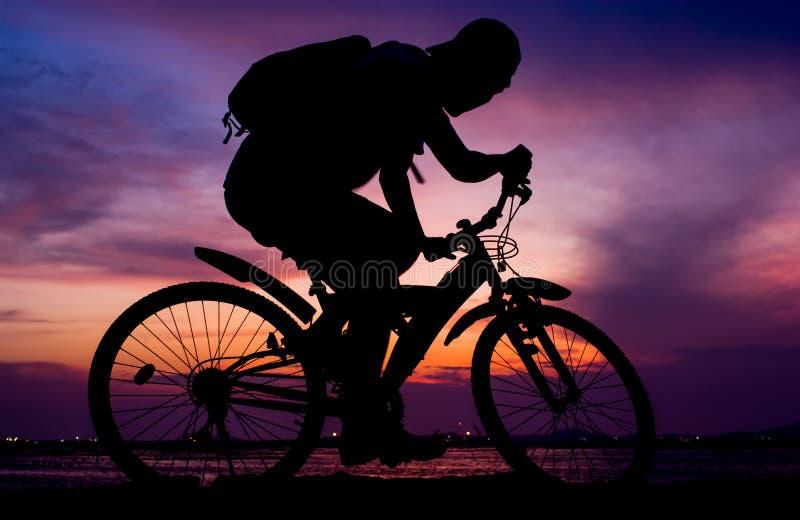 Siluetta del mountain bike di giro di viaggiatore con zaino e sacco a pelo accanto al mare fotografia stock