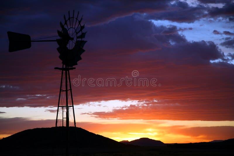 Siluetta del mulino a vento dell'azienda agricola al tramonto immagini stock