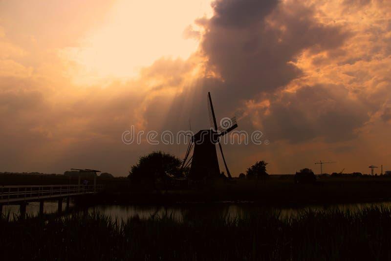 Siluetta del mulino a vento nell'ambito del tramonto immagine stock