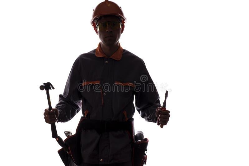 Siluetta del muratore con gli strumenti professionali, uomo i fotografie stock