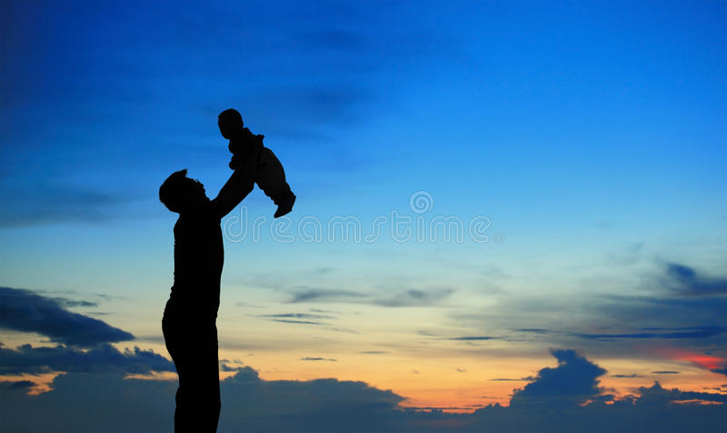 Siluetta del padre e del bambino sul tramonto di estate immagine stock