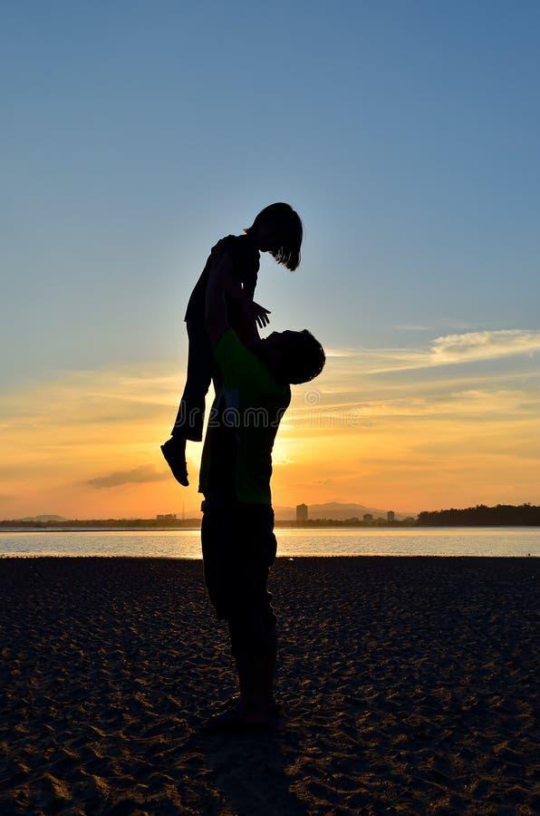 Siluetta del padre e della figlia sulla spiaggia immagini stock libere da diritti