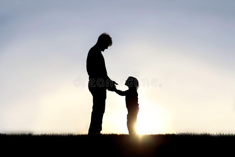Siluetta del padre ed il suo piccolo bambino felice che si tiene per mano e che sorride ad a vicenda fuori immagini stock libere da diritti