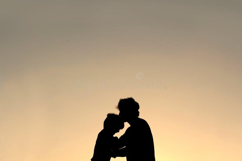 Siluetta del padre Kissing Young Child sulla fronte immagine stock