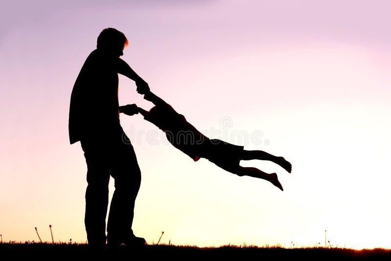 Siluetta del padre Playing con il bambino fuori al tramonto fotografie stock libere da diritti