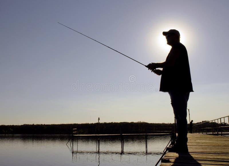 Siluetta del pescatore immagine stock
