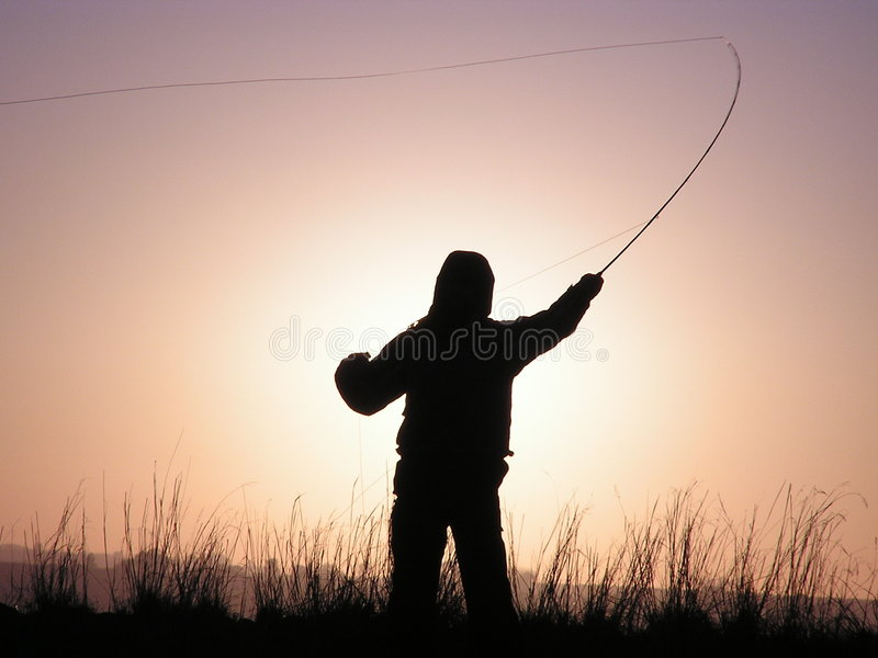 Siluetta del pescatore della mosca fotografia stock libera da diritti