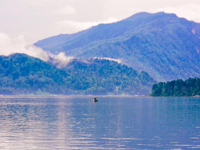 Siluetta del pescatore nella barca Pescatore che si inclina sul fiume Estate di vista superiore Paesaggio del fiume della natura  fotografia stock libera da diritti