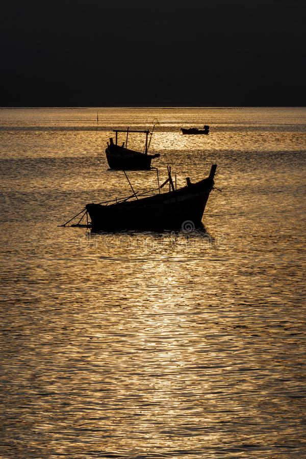 Siluetta del pilastro, barca con la regolazione del sole nel fondo con il cielo nuvoloso e variopinto, sole di Starlight sulla su fotografia stock