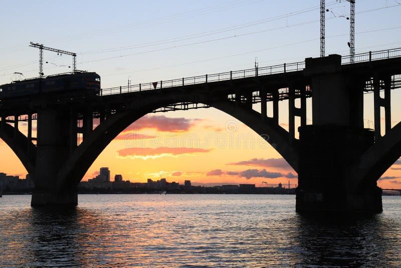 Siluetta del ponte ferroviario incurvato e di un treno al bello tramonto Fiume di Dnieper, città di Dnipo, Ucraina fotografia stock libera da diritti