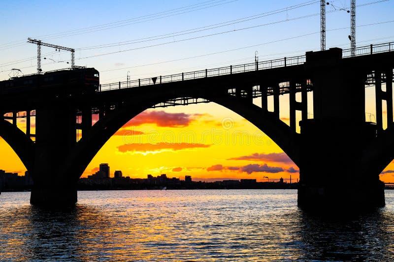Siluetta del ponte ferroviario incurvato e di un treno sul fiume di Dnieper al bello tramonto Dnipropetrovsk fotografia stock
