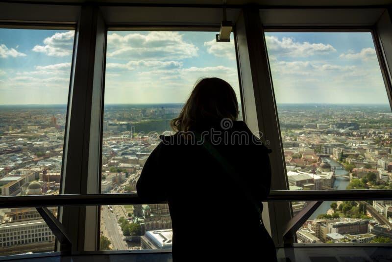 Siluetta del punto di vista posteriore della donna che esamina da una finestra fotografia stock